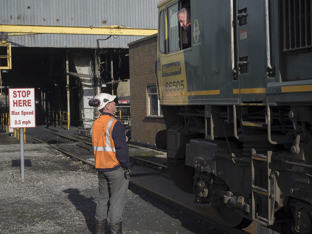 The train drives through the unloading shed at 0.5 mph. The coal is dropped onto a conveyor belt under the rails.